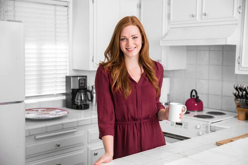 female posing in the kitchen with cup