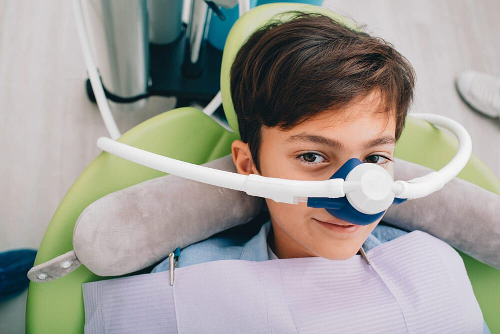 young child being put to sleep from sedative in dental office